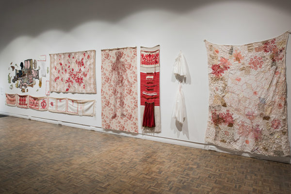 Torma - Anna Torma with Ilona Klocza, Red Fragments, Textile assemblage with Hungarian folk art, commercial and silkscreen prints, woman's handwork, hand embroidery on North American quilt patterns 2 cm x 9 m, photo by Steve Farmer (2017)