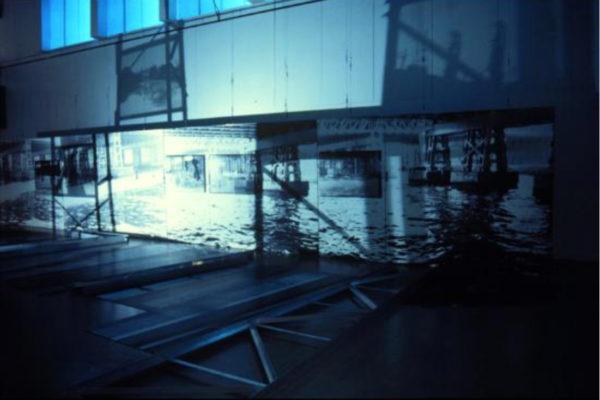 Claire Paquet and Suzanne Paquet. Comme les jours précédents, les géographies du transitoire (installation view, 2). Black and white photographs, aluminium scaffolding, light source (1996)