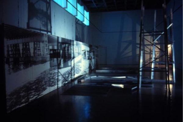 Claire Paquet and Suzanne Paquet. Comme les jours précédents, les géographies du transitoire (installation view, 3). Black and white photographs, aluminium scaffolding, light source (1996)