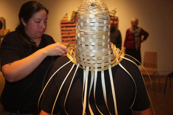 Ursula Johnson weaves a basketry portrait bust on a volunteer at MSVU Art Gallery. The work is part of the series K'nuwelti'k (We Are Indian) - (2014)