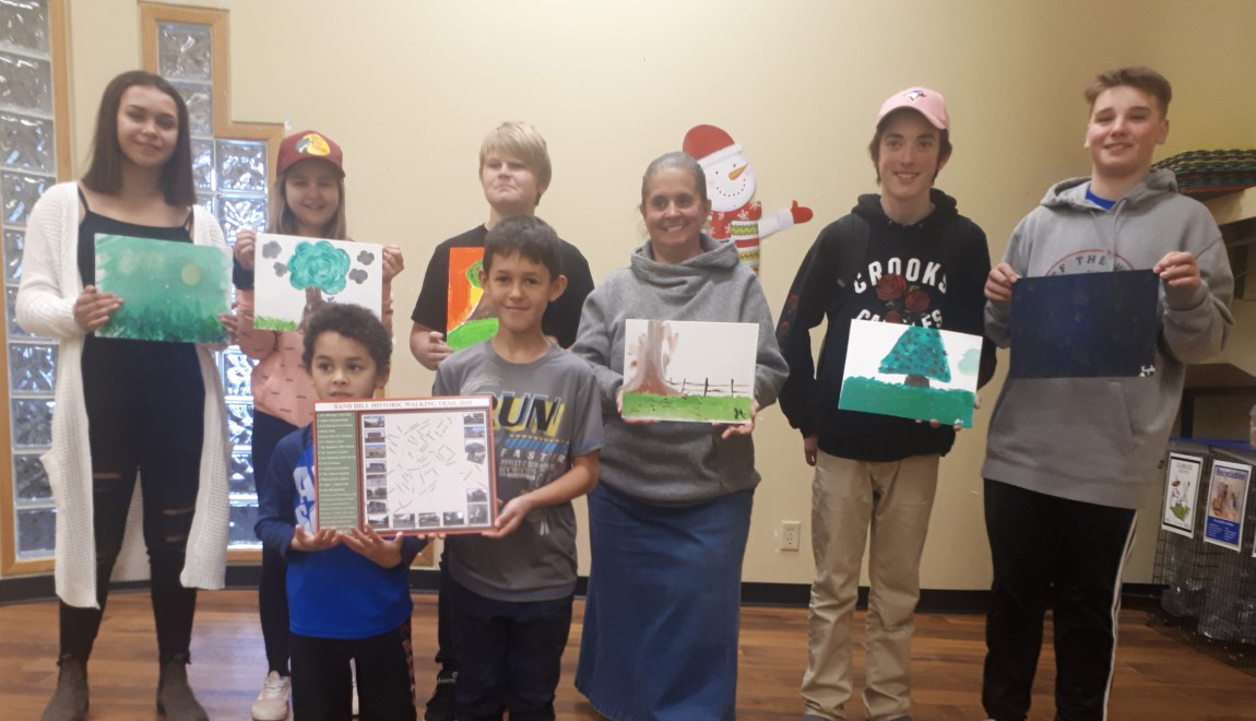 Photograph of 8 workshop participants of various ages, standing in a row, holding up their art